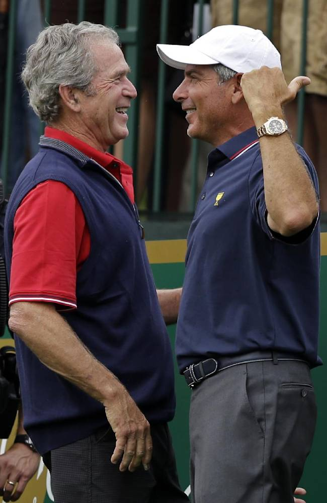 Former President George W. Bush, left, laughs with United States team captain Fred Couples before the start of the four-ball matches against the International team at the Presidents Cup golf tournament at Muirfield Village Golf Club Thursday, Oct. 3, 2013, in Dublin, Ohio