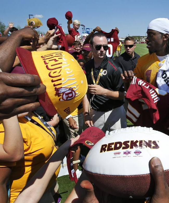 Washington Redskins quarterback Robert Griffin III, right, signs autographs for fans after practice at the team's NFL football training facility, Friday, July 25, 2014 in Richmond, Va. (AP Photo)