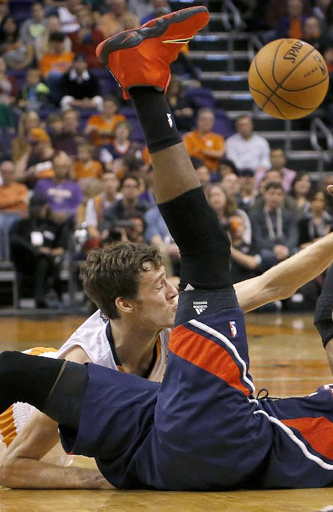 Atlanta Hawks' DeMarre Carroll, front, tries to pass the ball away from Phoenix Suns' Goran Dragic, of Slovenia, during the second half of an NBA basketball game, Sunday, March 2, 2014, in Phoenix. The Suns won 129-120