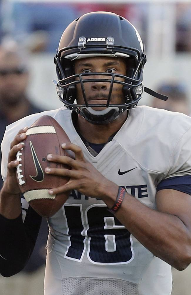 In this Aug. 29, 2013, file photo, Utah State quarterback Chuckie Keeton (16) looks down field in the first quarter of an NCAA football game against Utah in Salt Lake City.  By the time Southern California coach Lane Kiffin was done talking this week, the Trojans and their fans were certain Utah State is a BCS title contender and quarterback Chuckie Keeton is a Heisman Trophy front-runner