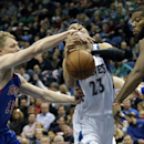 Minnesota Timberwolves' Kevin Martin, center, loses the ball as he is double-teamed by Detroit Pistons' Kyle Singler, left, and Greg Monroe in the first quarter of an NBA basketball game, Friday, March 7, 2014, in Minneapolis The Associated Press