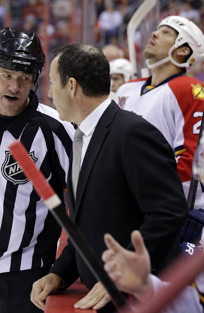 Referee Dave Jackson talks with Florida Panthers coach Kevin Dineen during a timeout in the third period of the Panthers' NHL hockey game against the Washington Capitals, Saturday, Nov. 2, 2013, in Washington. The Capitals won 3-2 in a shootout