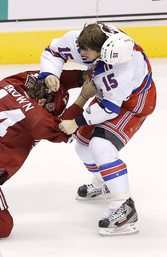 New York Rangers' Derek Dorsett (15) fights with Phoenix Coyotes' Chris Brown in the third period during an NHL hockey game on Thursday, Oct. 3, 2013, in Glendale, Ariz.  The Coyotes defeated the Rangers 4-1