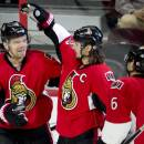 Ottawa Senators defenseman Erik Karlsson, center, and Bobby Ryan, right, congratulate teammate Milan Michalek on his goal against Anaheim Ducks goalie Ilya Bryzgalov during the first period of an NHL hockey game Friday, Dec. 19, 2014, in Ottawa, Ontario. (AP Photo/The Canadian Press, Adrian Wyld)