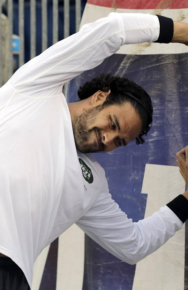 New York Jets injured quarterback Mark Sanchez stretches along a stadium wall before an NFL football game between the Jets and the New England Patriots Thursday, Sept. 12, 2013, in Foxborough, Mass