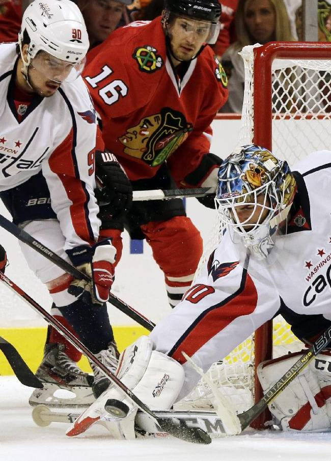 Washington Capitals goalie Braden Holtby (70) blocks a shot by Chicago Blackhawks' Ben Smith (28) as Washington Capitals' Marcus Johansson (90) and Chicago Blackhawks' Marcus Kruger (16) look on during the second period of an NHL preseason hockey game in Chicago, Saturday, Sept. 28, 2013