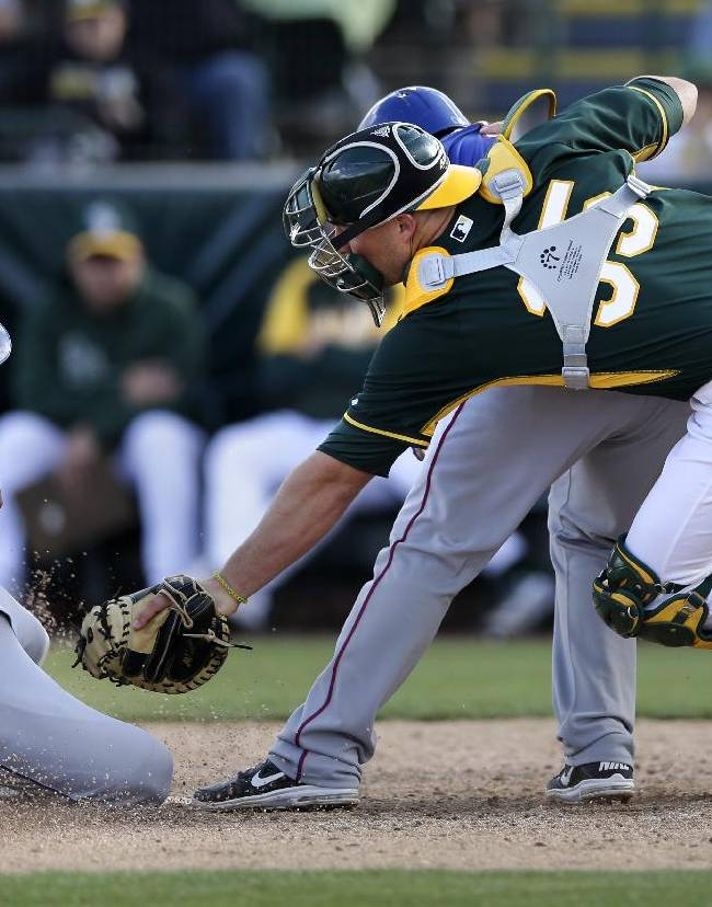 Oakland Athletics catcher Chris Gimenez, right, leaps past Texas Rangers' Jose Felix, center, as he tags out Alex Castellanos, left, caught trying to steal home during the eighth inning of a spring training baseball game Saturday, March 1, 2014, in Phoenix