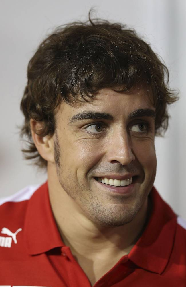 Ferrari driver Fernando Alonso of Spain smiles as he walks outside the team paddock before the Singapore Formula One Grand Prix on the Marina Bay City Circuit, Thursday, Sept. 19, 2013 in Singapore. F1 Singapore Grand Prix will be held Sunday