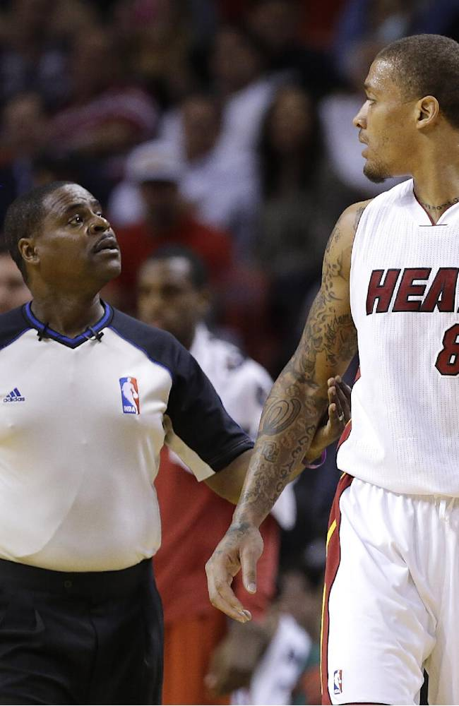 Official Leroy Richardson, center, talks with Miami Heat's Michael Beasley (8) after he was called with a foul during the first half of an NBA basketball game against the Milwaukee Bucks, Tuesday, Nov. 12, 2013, in Miami. At left is Dwyane Wade (3)