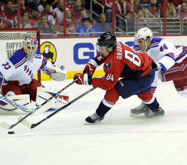 New York Rangers defenseman Justin Falk (44) battles for the puck against Washington Capitals center Mikhail Grabovski (84), of Germany, during the first period an NHL hockey game, Friday, Dec. 27, 2013, in Washington. Also seen is Rangers goalie Cam Talbot (33)