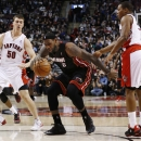 Miami Heat's LeBron James, center, is guarded by Toronto Raptors' Terrence Ross, back left, Tyler Hansbrough, center left, Kyle Lowry, center right, and Rudy Gay during the first half of an NBA basketball game in Toronto, Friday, Nov. 29, 2013 The Associa