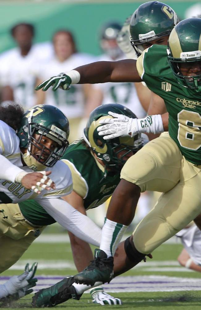 Colorado State running back Chris Nwoke, right, breaks past Cal Poly cornerback Bijon Samoodi, front left, and defensive back Alex Hubbard for a long gain in the fourth quarter of Colorado State's 34-17 victory in an NCAA college football game in Fort Collins, Colo., on Saturday, Sept. 14, 2013