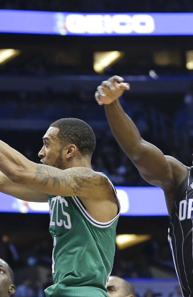 Boston Celtics' Courtney Lee, left, gets a shot off in front of Orlando Magic's Victor Oladipo (5) during the first half of an NBA basketball game in Orlando, Fla., Friday, Nov. 8, 2013