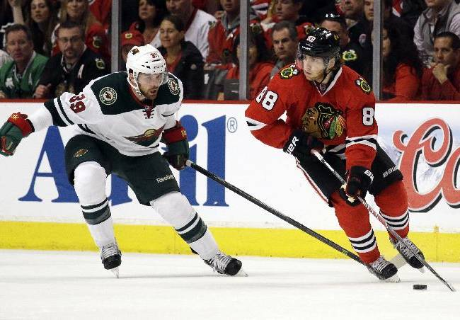 Chicago Blackhawks' Patrick Kane (88), right, controls the puck as he looks to a pass against Minnesota Wild's Nate Prosser (39) during the first period  in Game 2 of an NHL hockey second-round playoff series in Chicago, Sunday, May 4, 2014