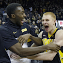 Iowa forward Aaron White, right, celebrates with teammate Gabriel Olaseni after an NCAA college basketball game against Notre Dame, Tuesday, Dec. 3, 2013, in Iowa City, Iowa. White scored 20 points as Iowa won 98-93. (AP Photo/Charlie Neibergall)