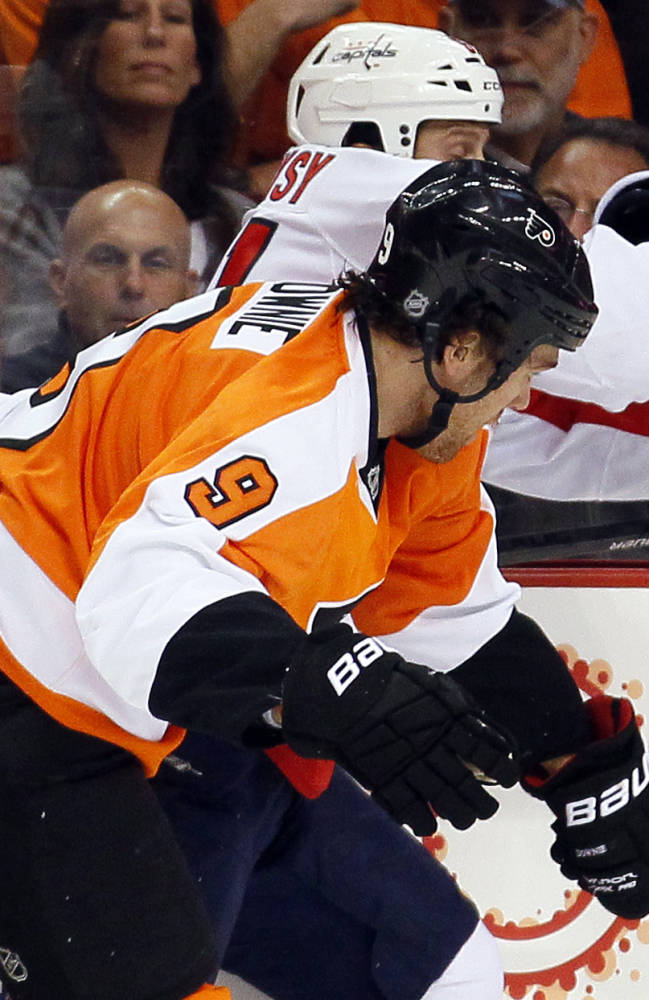 Philadelphia Flyers' Steve Downie, front, checks Washington Capital's  Steve Olesky into the board during the first period of an NHL hockey game, Friday, Nov. 1, 2013, in Philadelphia. Downie, a former Flyer, was acquired on Oct. 31 in a trade with the Colorado Avalanche for Maxime Talbot