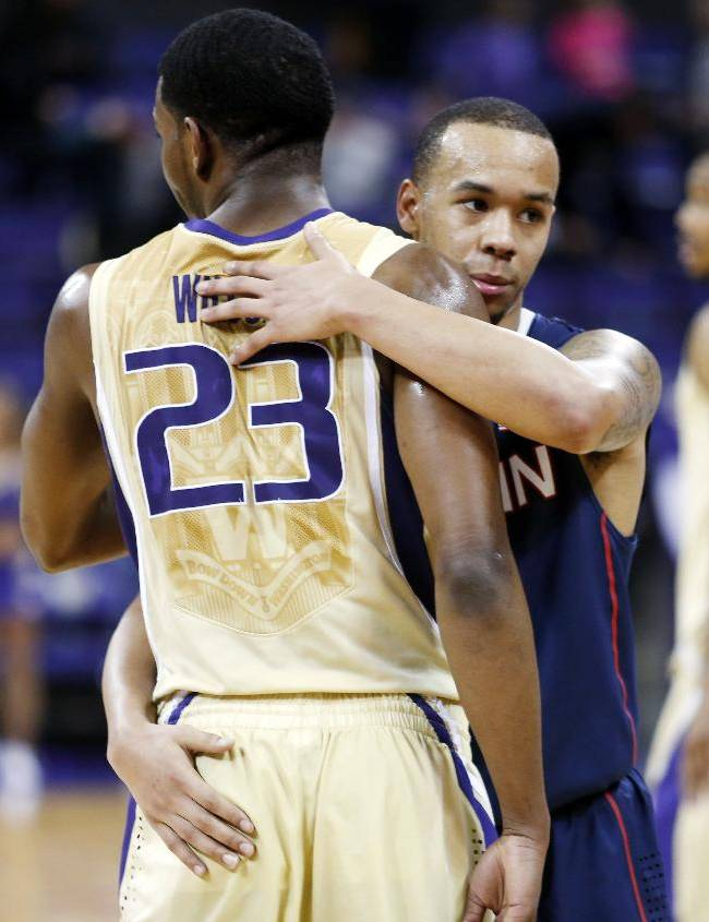Connecticut's Shabazz Napier, right, hugs Washington's C.J. Wilcox at the end of an NCAA college basketball game in Seattle on Sunday, Dec. 22, 2013. UConn won 82-70