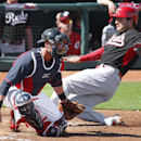 Cincinnati Reds' Joey Votto, right, scores as Cleveland Indians catcher Yan Gomes is late with the tag at home plate on a Ryan Ludwick single in the third inning of an exhibition baseball game in Goodyear, Ariz., Wednesday, Feb. 26, 2014 The Associated Pr