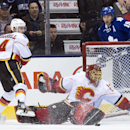 Calgary Flames goalie Jonas Hiller, front, makes a save as Flames defenceman Kris Russell (4) and Toronto Maple Leafs forward Joffrey Lupul, back, look on during the first period of an NHL hockey game in Toronto on Tuesday, Dec. 9, 2014 The Associated Pre