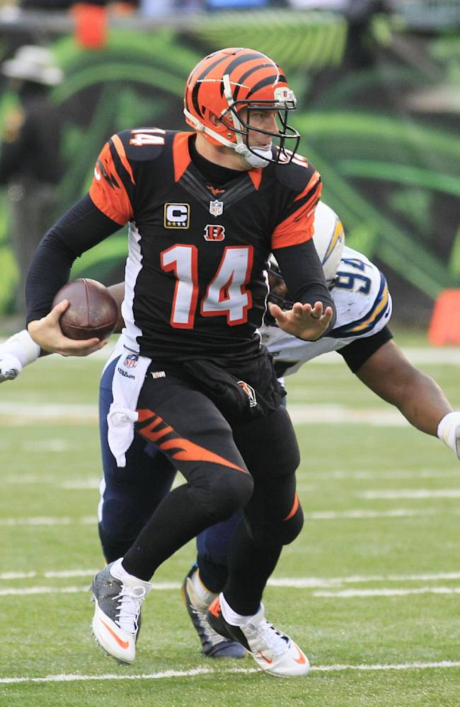 Cincinnati Bengals quarterback Andy Dalton (14) is chased by San Diego Chargers defensive end Corey Liuget in the second half of an NFL wild-card playoff football game on Sunday, Jan. 5, 2014, in Cincinnati