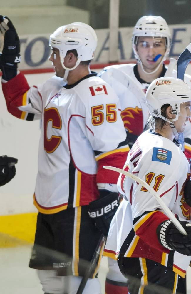 Calgary Flames center Corban Knight, defenseman Shane O'Brien, right winger Emile Poirier, forward Mikael Backlund, and defenseman Chris Butler, from left, celebrate a goal against the New York Islanders during the second period of a preseason NHL hockey game Tuesday, Sept. 17, 2013, in Regina, Saskatchewan