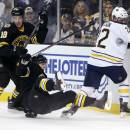 Boston Bruins' Reilly Smith (18), Torey Krug, center, and Buffalo Sabres Johan Larsson (22) battle along the boards in the first period of an NHL hockey game in Boston, Sunday, Dec. 21, 2014. (AP Photo/Michael Dwyer)