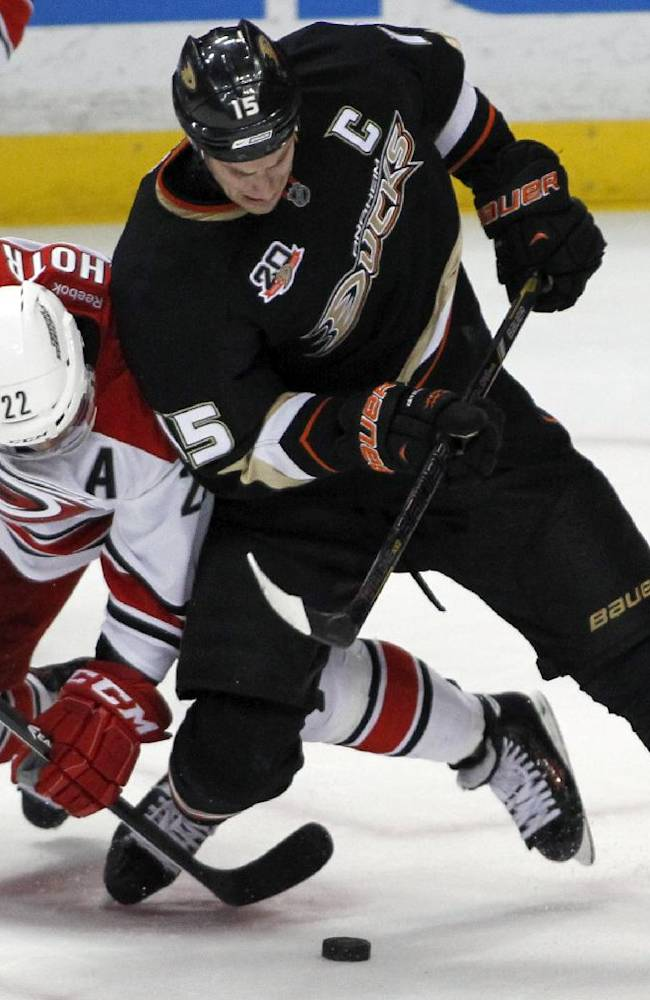 Carolina Hurricanes center Manny Malhotra (22) and Anaheim Ducks center Ryan Getzlaf (15) vie for the puck during the third period of an NHL hockey game Sunday, March 2, 2014, in Anaheim, Calif. The Ducks won 5-3
