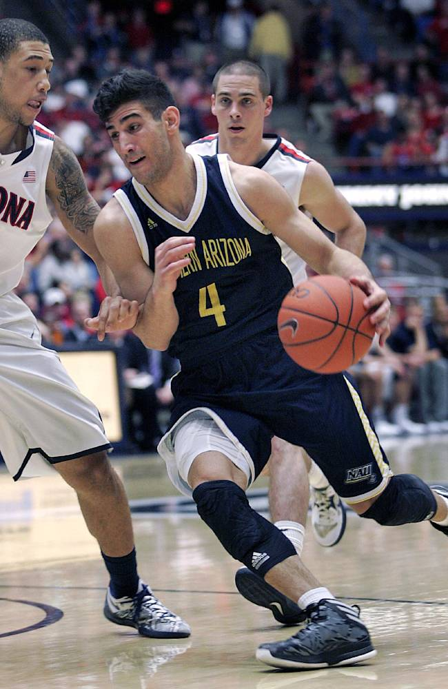 Northern Arizona's Kris Yanku (4) drives in the lane against the defense of Arizona's Brandon Ashley (21) in the second half of an NCAA college basketball game on Monday, Dec. 23, 2013, in Tucson, Ariz. Arizona won 77 - 44