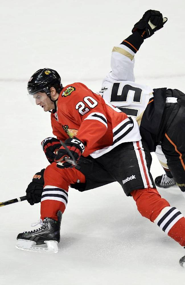 Chicago Blackhawks left wing Brandon Saad, left, and Anaheim Ducks center Ryan Getzlaf fall to the ice as they struggle for position on a Saad breakaway during overtime of an NHL hockey game Friday, Dec. 6, 2013, in Chicago. No penalty was called. The Ducks won 3-2 in a shootout