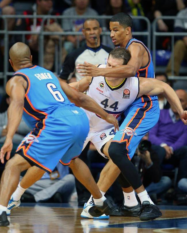 The NBA team Oklahoma City Thunder's Derek Fisher, left, and Andre Roberson, right,   fight for the ball during with Fenerbahce Ulker's Bojan Bogdanovic during a preseason basketball game in Istanbul, Turkey, Saturday, Oct. 5, 2013. Oklahoma City Thunder has opened the preseason schedule with a game against the five-time Turkish champions at the Ulker Sports Arena.(AP Photo)