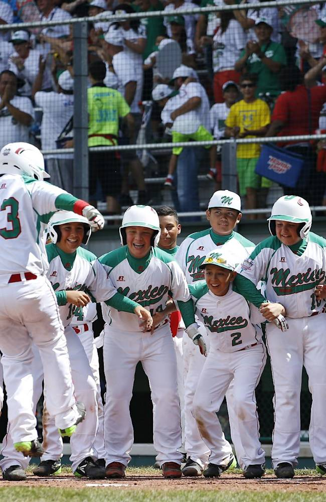 Mexico's Erick Vela (23) leaps onto home plate after hitting a three-run home run during the fourth inning of an International elimination baseball game against Australia at the Little League World Series, Monday, Aug. 18, 2014, in South Williamsport, Pa. Mexico won 6-2