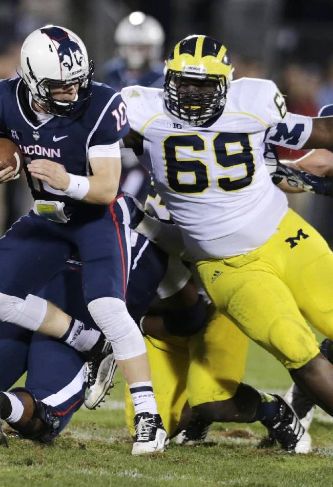 Michigan defensive tackle Willie Henry (69) chases down Connecticut quarterback Chandler Whitmer (10) during the second half of an NCAA college football game, Saturday, Sept. 21, 2013, in East Hartford, Conn. Michigan won 24-21