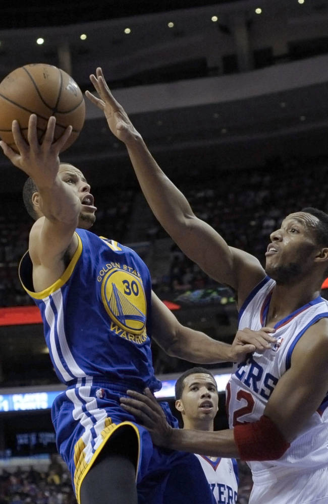 Golden State Warriors' Stephen Curry (30) drives to the basket past Philadelphia 76ers' Evan Turner (12) during the first half of an NBA basketball game on Monday, Nov. 4, 2013, in Philadelphia