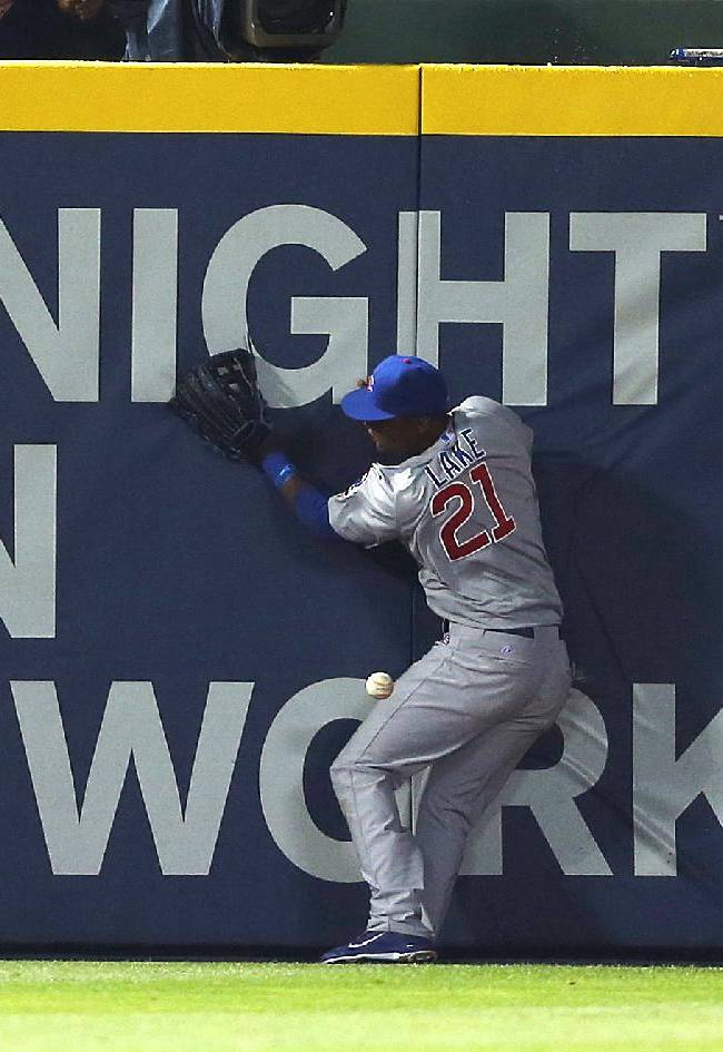 Chicago Cubs left fielder Junior Lake (21) cannot reach a ball hit for an RBI-double by Atlanta Braves pinch hitter Ryan Doumit in the seventh inning of a baseball game on Saturday, May 10, 2014, in Atlanta