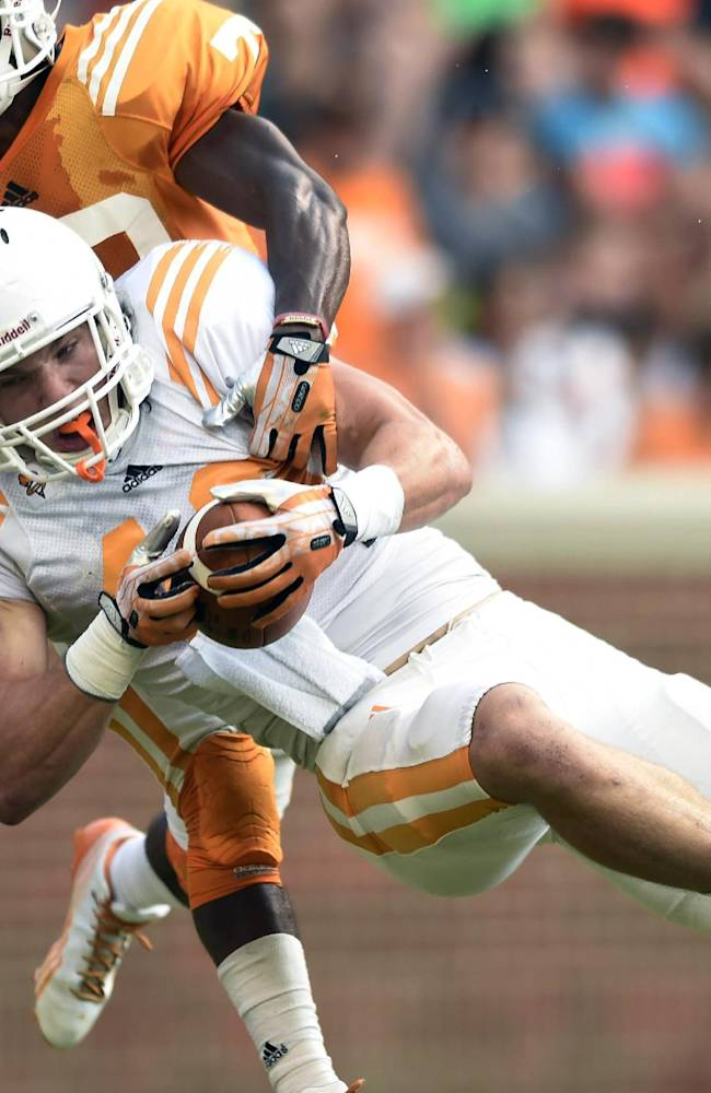 Tennessee tight end Alex Ellis (40) makes a reception against Tennessee defensive back Malik Foreman (22) during Tennessee's open practice at Neyland Stadium in Knoxville on Saturday, Aug. 16, 2014