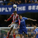 Chelsea's Nemanja Matic, right, competes with Stoke City's Peter Crouch during their English Premier League soccer match at Stamford Bridge, London, Saturday, April 5, 2014