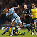 Manchester City's Vincent Kompany, centre, fouls Arsenal's Olivier Giroud for which he is shown a yellow card during the English Premier League soccer match between Manchester City and Arsenal at the Etihad Stadium, Manchester, England, Sunday, Jan. 18, 2