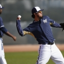 Milwaukee Brewers' Yovani Gallardo, right, makes a warm up long toss as teammate Ariel Pena waits for a throw during Brewers spring training baseball practice, Thursday, Feb. 20, 2014, in Phoenix The Associated Press