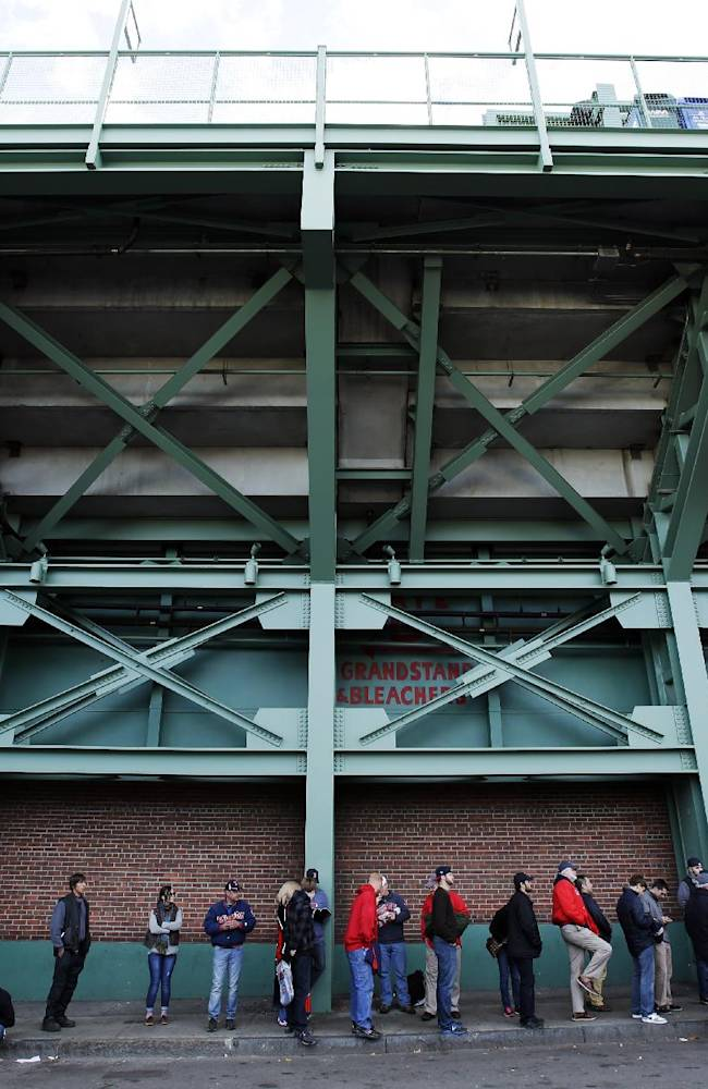 Fans line up under the Green Monster to get into Fenway Park before Game 2 of baseball's World Series between the Boston Red Sox and the St. Louis Cardinals Thursday, Oct. 24, 2013, in Boston