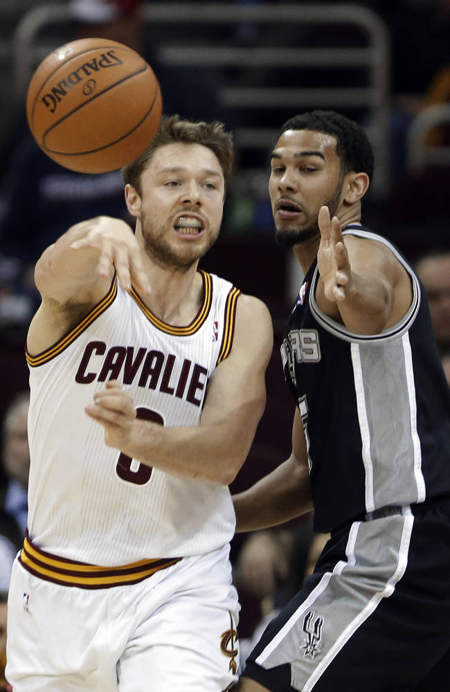 Cleveland Cavaliers' Matthew Dellavedova, left, fires a pass away from San Antonio Spurs' Cory Joseph during the fourth quarter of an NBA basketball game Tuesday, March 4, 2014, in Cleveland. The Spurs won 122-101