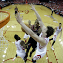 Portland Trail Blazers' Damian Lillard, center, goes up for a shot as Houston Rockets' Omer Asik, right, and James Harden (13) defend during the second half in Game 1 of an opening-round NBA basketball playoff series Sunday, April 20, 2014, in Houston. Th