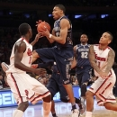 Georgetown's Otto Porter Jr., center goes up against St. Johns' Sir Dominic Pointer, left, and D'angelo Harrison during the first half of an NCAA college basketball game, Saturday, Jan. 12, 2013, at Madison Square Garden in New York. Porter had 19 points and a season-high 14 rebounds and No. 19 Georgetown broke out of its scoring funk with a 67-51 victory. (AP Photo/Mary Altaffer)