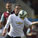 Manchester United's Robin van Persie, centre, keeps the ball from Burnley's Jason Shackell during their English Premier League soccer match at Turf Moor Stadium, Burnley, England, Saturday Aug. 30, 2014