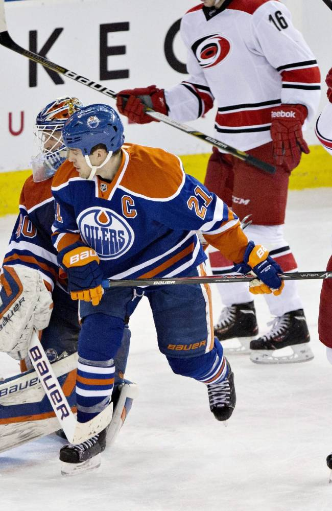 Carolina Hurricanes' Manny Malhotra (22) celebrates a goal against Edmonton Oilers goalie Devan Dubnyk (40) as Oilers' Andrew Ference (21) looks to the net during third period NHL hockey action in Edmonton, Alberta, on Tuesday, Dec. 10, 2013