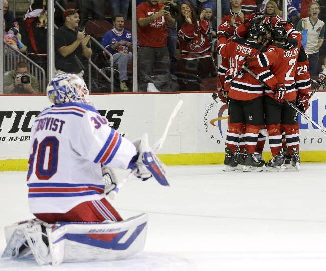 Members of the New Jersey Devils celebrate a goal by right wing Dainius Zubrus, of Lithuania, as New York Rangers goalie Henrik Lundqvist, left, of Sweden, kneels in his crease during the second period of an NHL hockey game, Saturday, Oct. 19, 2013, in Newark, N.J