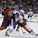Edmonton Oilers center Derek Roy, center, fight for the puck with Florida Panthers defenseman Erik Gudbranson (44) and center Derek MacKenzie, right, in the first period of an NHL hockey game, Saturday, Jan. 17, 2015, in Sunrise, Fla The Associated Press