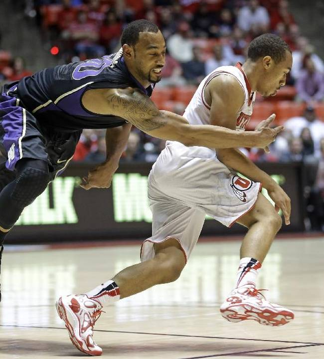 Utah's Brandon Taylor, right, drives past Washington's Desmond Simmons during the second half of an NCAA college basketball game Thursday, Feb. 6, 2014, in Salt Lake City. Utah won 78-69