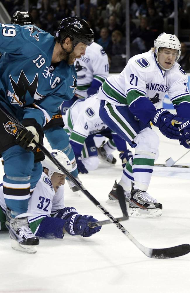 San Jose Sharks' Joe Thornton (19) is defended by Vancouver Canucks' Dale Weise (32) and Zac Dalpe (21) during the first period of an NHL hockey game Thursday, Oct. 3, 2013, in San Jose, Calif