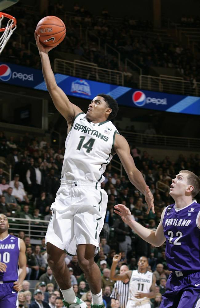 Michigan State's Gary Harris (14) puts up a layup against Portland Ryan Nicholas (32) during the first half of an NCAA college basketball game, Monday, Nov. 18, 2013, in East Lansing, Mich