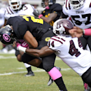 In this Saturday, Oct. 26, 2013, file photo, Grambling running back Cedric Skinner (23) runs as Texas Southern defensive lineman Amir Bloom (44) stops him in the first half of an NCAA college football game in Grambling, La. After a turmoil-filled 2013 sea